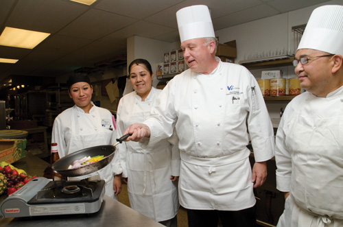 Chef cooking as mentors watch