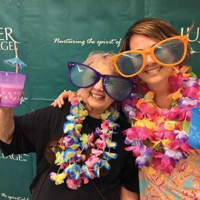 Anne Campbell (R) and coworker Finch VanDivier celebrate Juniper Anniversary Week with margaritas and a photo booth.